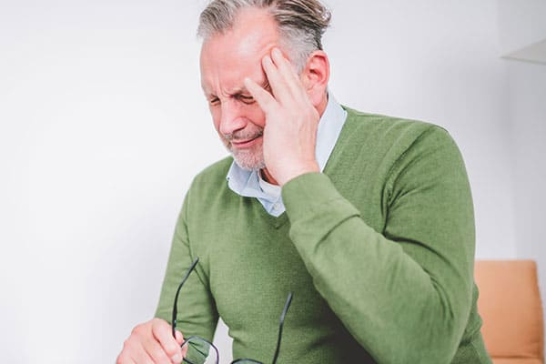 Mann greift sich an Schläfe wegen Kopfschmerzen