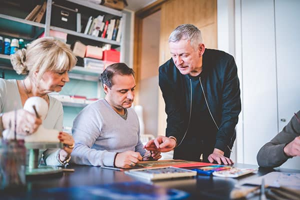 Therapeut erklärt Patient etwas bei der Kunsttherapie