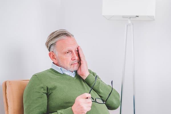 Mann reibt sich die Augen - Müdigkeit ist ein Symptom von Depression