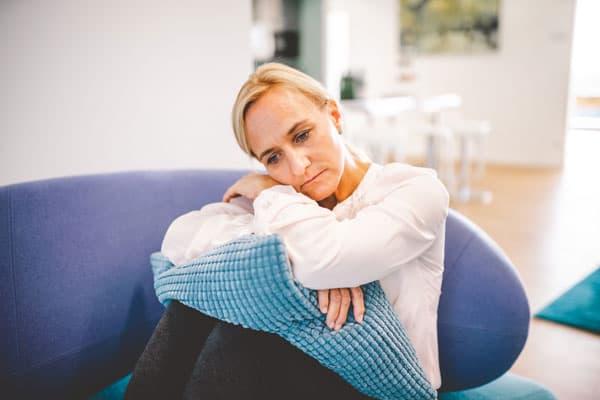 Frau mit Depression sitzt auf Sofa